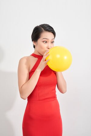 Happy emotional young asian woman in red is blowing a yellow balloon in studio. Portrait of beautiful vietnamese girl. Shopping concept Banco de Imagens