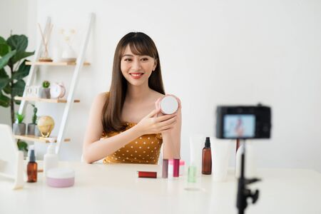 Asian beauty blogger recording video at home