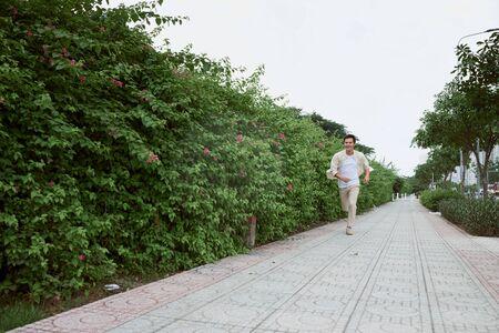 Lächelnder junger Mann, der im Sommer im Park läuft