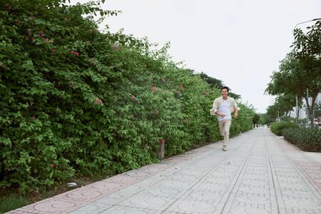 Smiling young man running in the park during summer