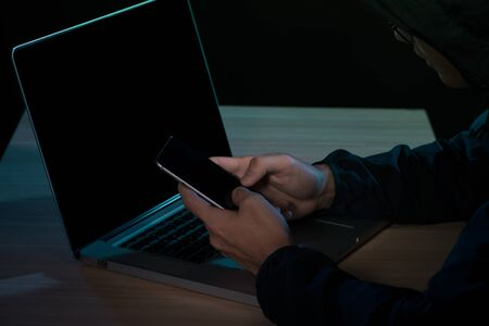 Hacker using a smartphone. Very dark nocturnal environment