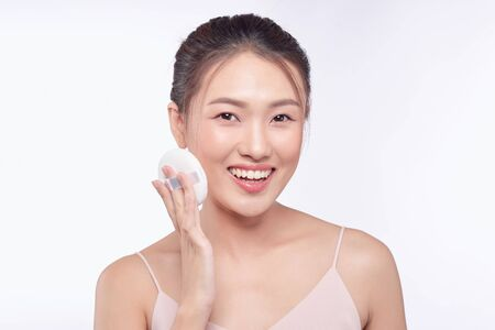 face of beauty young woman applying sponge - isolated on white