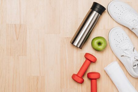 Dumbbells, bottle of water and skipping rope on blue background. Top view. Fitness, sport and healthy lifestyle concept.