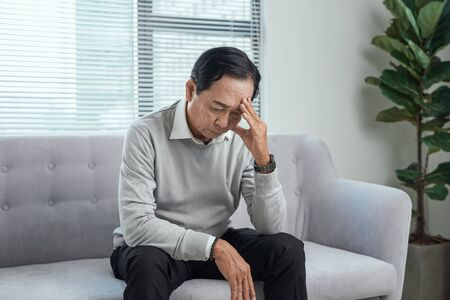 health care, stress, old age and people concept - senior man suffering from headache at home 免版税图像