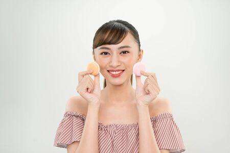 Portrait of happy Asian woman holding Macaroons