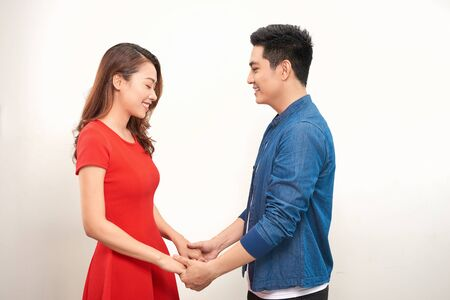 Happy young couple holding hands and laughing on white background