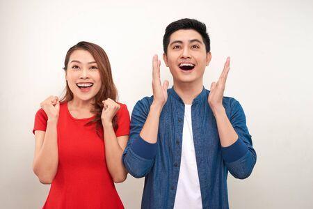 Jong Aziatisch paar verliefd op geïsoleerde achtergrond vieren verrast en verbaasd over succes met opgeheven armen en open ogen