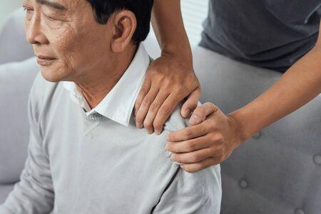 Dolor en el hombro del anciano asiático, sentado en el sofá, hijo masajeando el hombro del padre. Foto de archivo