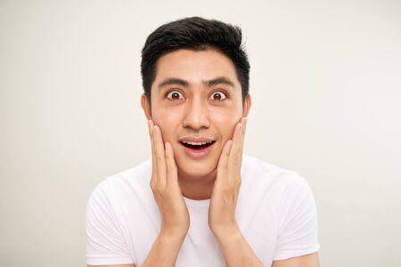 Hübscher asiatischer Mann berührt sein Gesicht und lächelt, während er in den Spiegel schaut