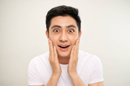 Handsome Asian man is touching his face and smiling while looking into the mirror