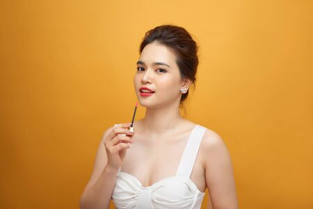 Perfect girl holding lipstick on yellow background, close up portrait.