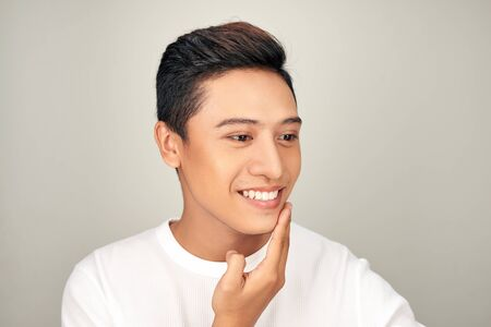 Portrait of shirtless young handsome Asian man checking his face for skin care and beauty concepts on white background Stock Photo