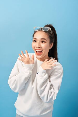 Happy woman keeps hands under chin looks joyfully at camera, notices something very pleasant, isolated over light blue background Фото со стока