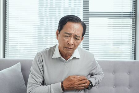 Old man feel pain in their heart  in living room, medical concept
