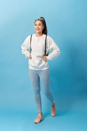 Full length photo of asian woman student walking with backpack isolated over light blue background