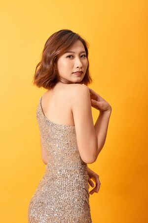 Fashion photo of asian woman in luxurious glitter golden dress. Sexy party body