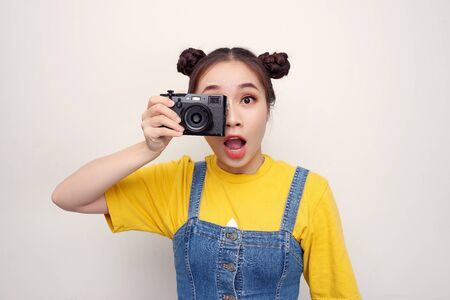 Image of excited paparazzi girl  holding retro camera at face and photographing isolated over white background