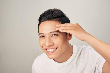 Schöner Mann, der sein Gesicht berührt, Nahaufnahme Porträtstudio auf weißem Hintergrund Standard-Bild