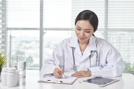 smiling female doctor writing document at workplace in office Stock Photo