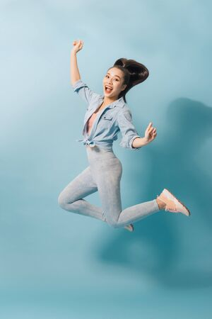 Full length portrait of a joyful young woman jumping and celebrating over light blue background 版權商用圖片 - 126710479
