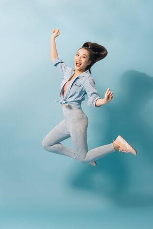 Portrait complet d'une joyeuse jeune femme sautant et célébrant sur fond bleu clair