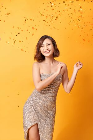 beautiful sexy woman in evening dress celebrating, golden confetti, party, smiling, inviting, happy Imagens