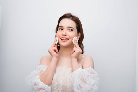 Beautiful young smiling woman with clean cotton pads . Facial treatment. Beauty skin care famale face . Expressive facial expressions. Imagens