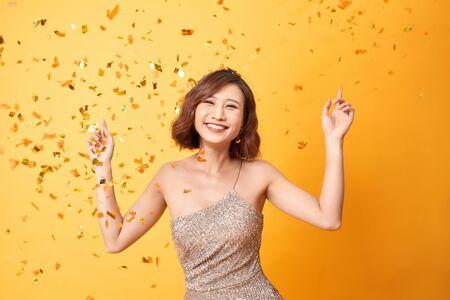 Mujer joven bailando bajo confeti en casa, celebrando un cumpleaños