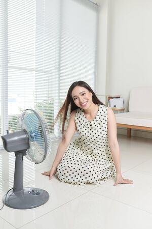 beauty young woman sitting on living room and using electric fan enjoying cool wind Stock fotó