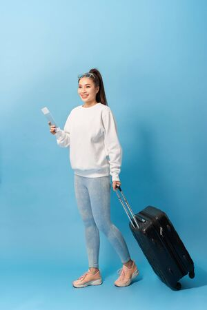 Portrait of trendy young girl standing with suitcase and holding passport with tickets, over blue background