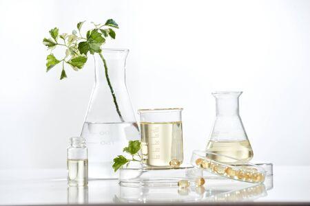 El científico o el médico elaboran hierbas medicinales a partir de hierbas en el laboratorio sobre la mesa. Tratamiento alternativo. Mostrar mano y estetoscopio. con el envase de la botella Foto de archivo