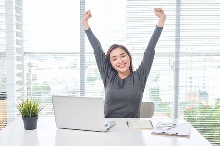 Zadowolona kobieta relaksuje z rękami za głową. Szczęśliwy uśmiechnięty pracownik po skończeniu pracy, przeczytaniu dobrych wiadomości, przerwie w pracy, dziewczynie wykonującej proste ćwiczenia, łagodzeniu stresu mięśniowego, dobrym samopoczuciu
