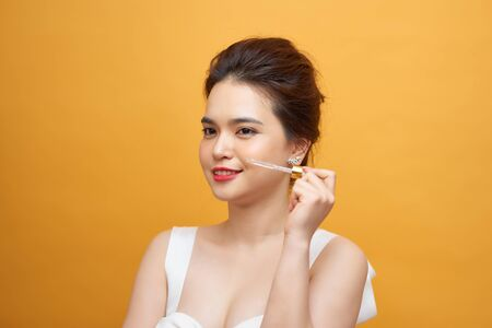 young beautiful asian woman hold pipette of serum for skin on yellow background