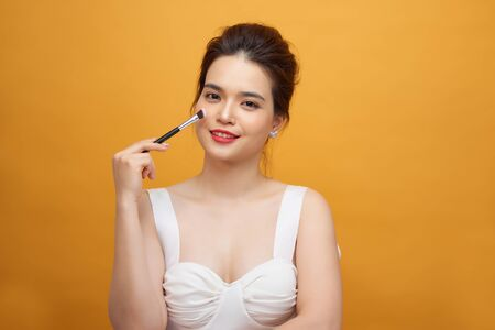 Woman applying make up with brush, isolated. Beauty procedures