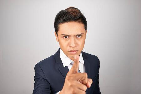Uomo d'affari asiatico arrabbiato su sfondo bianco