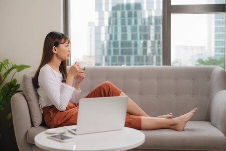Young woman in casual clothes sitting on sofa at cozy home interior. Technology and communication concept. Stock fotó