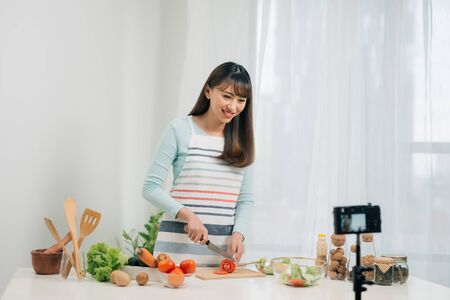 Online cooking classes. Food blogging. Woman preparing meal and shooting video tutorial on camera.
