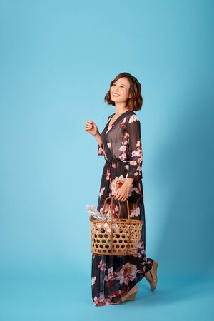 Beautiful young smiling woman in vintage dress holding a basket with flowers. Summer portrait pretty young girl. 写真素材