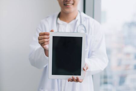 happy young doctor holding tablet
