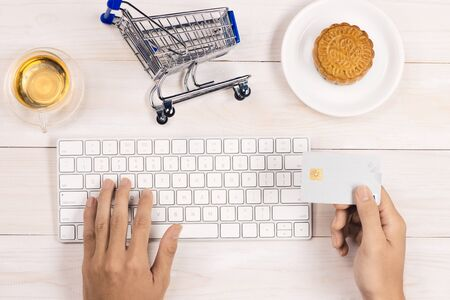 Online shopping concept. Computer keyboard, shopping cart, cake and tea with copy space. Imagens