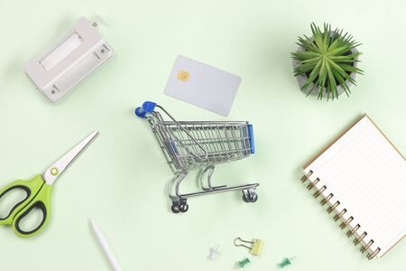 Shopping cart with credit cards on old wood background.