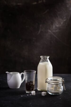 A jug  bottle of milk, glass of bubble and a sugar pot on black table Stock Photo