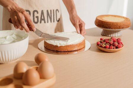 Uomo che mette la crema sul pan di spagna. Processo di preparazione della torta fatta in casa