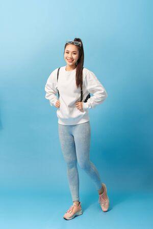 Foto de cuerpo entero de una estudiante asiática caminando con mochila aislado sobre fondo azul claro