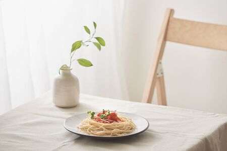 handmade pasta with ragout sauce on plate on vintage white table with colander and flowers