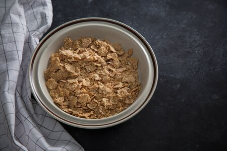 Wheat bran breakfast cereal with no milk in a bowl. Black background with homespun napkin.
