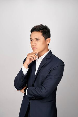 Retrato de atractivo joven empresario asiático es confuso sobre fondo blanco. Foto de archivo
