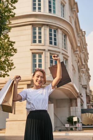 Blissful shopaholic woman dancing on the street with smile. Фото со стока - 127712329