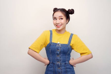 Portrait of beautiful young Asian woman with hair buns and looking flirty at camera on white background