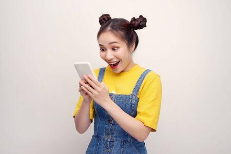 Mooi levendig meisjesachtig gelukkig lachend meisje dat sms-melding leest over winnen, geïsoleerd op witte achtergrond